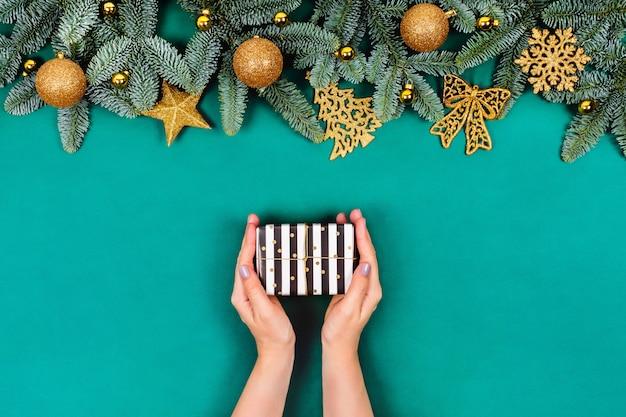Grüner weihnachtstisch mit händen und geschenk.