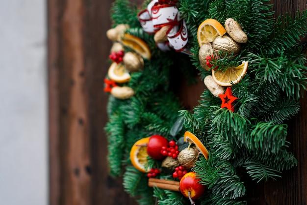 Grüner weihnachtstürkranz mit zimtstangen und getrockneten orangen