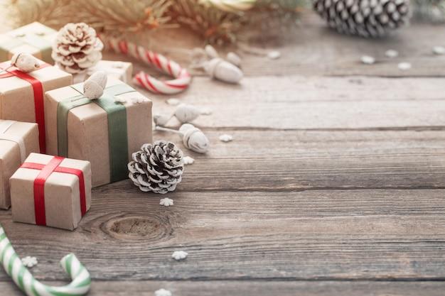 Grüner weihnachtszweig und geschenke auf hölzernem hintergrund
