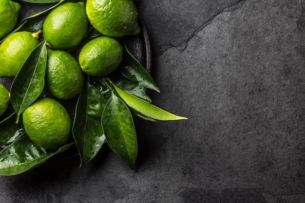 Grüner zitronen-kalk mit frischen blättern auf schwarzblech, schieferhintergrund