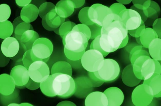 Grünes abstraktes weihnachten unscharfer leuchtender hintergrund. defocused künstlerisches bokeh beleuchtet bild