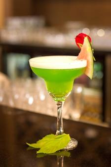 Grünes alkoholisches cocktail mit minze in einem margaritaglas auf einem barzähler