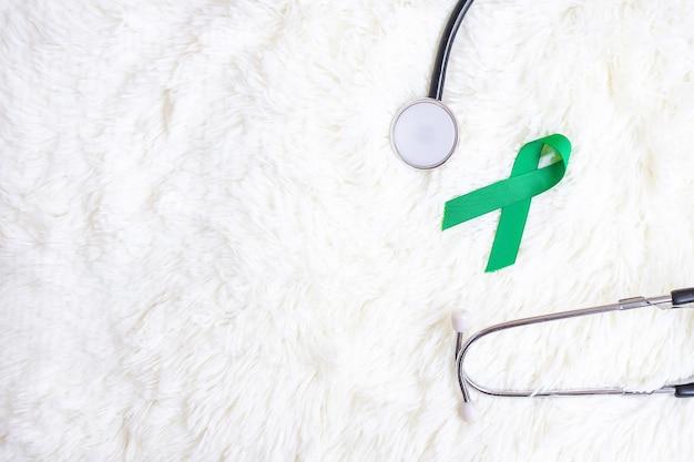 Grünes band mit stethoskop auf weißem hintergrund zur unterstützung von menschenleben und krankheit. leber, gallenblase, gallengang krebs und organspende konzept des bewusstseinsmonats