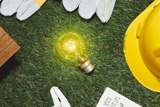 Grünes bauen und energiesparkonzept: hausprojekt und arbeitsgeräte auf dem gras