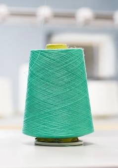 Grünes baumwollgarn bei der arbeit an einer strickmaschine.