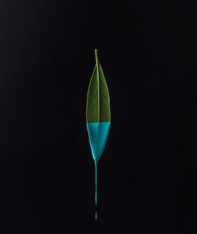 Grünes blatt mit tropfender blauer farbe auf dunkler oberfläche