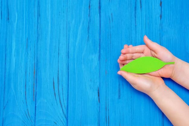 Grünes blatt papier in den händen des kindes.