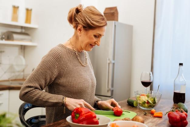 Grünes brett. lächelnde reife dame mit gebundenem haar, die sich mit einem langen messer beschäftigt, während sie eine mahlzeit für sich selbst kocht