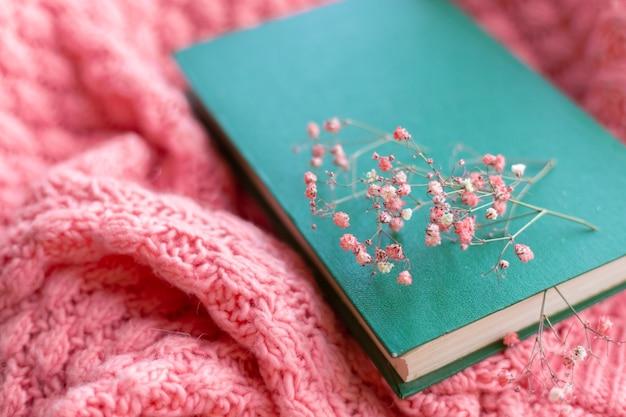 Grünes buch mit trockenen blumen auf einem rosa warmen strickpullover