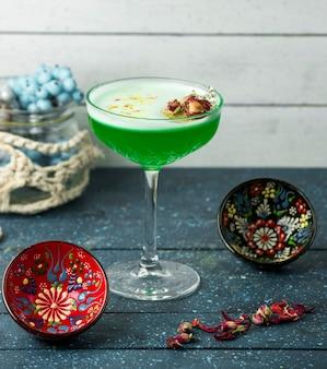 Grünes cocktail mit haselnüssen auf dem tisch