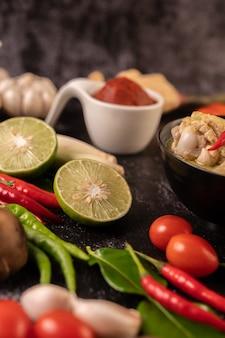 Grünes curry aus hühnchen, chili und basilikum mit tomaten, kaffirlimettenblättern und knoblauch. fokus limette
