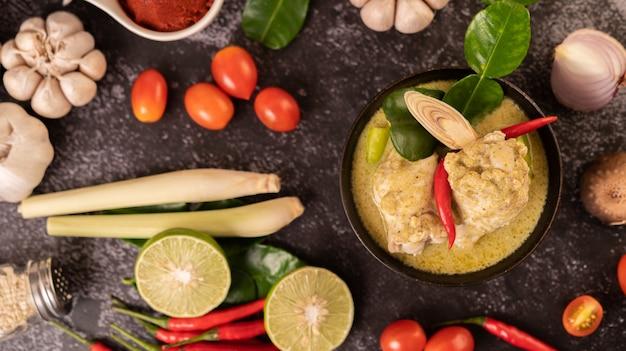 Grünes curry aus hühnchen, chili und basilikum mit tomaten, limetten, kaffirlimettenblättern und knoblauch.