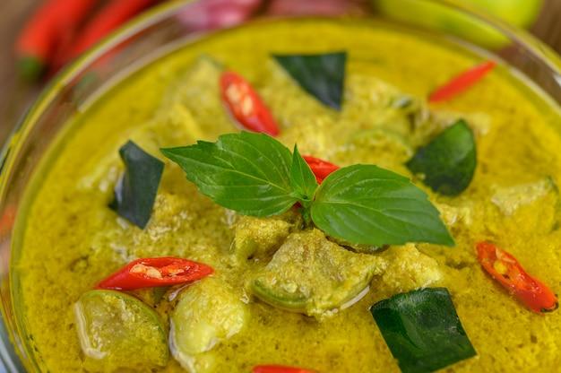 Grünes curry in einer schüssel auf holztisch.