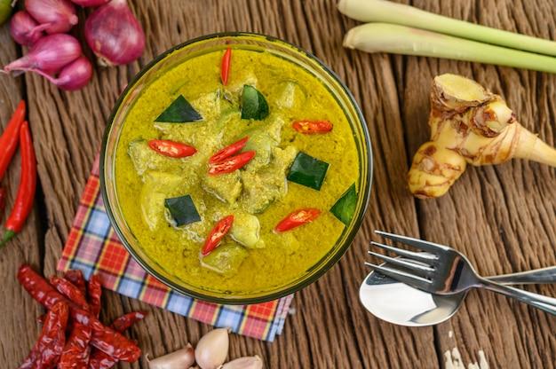 Grünes curry in einer schüssel mit gabel und löffel auf holztisch.