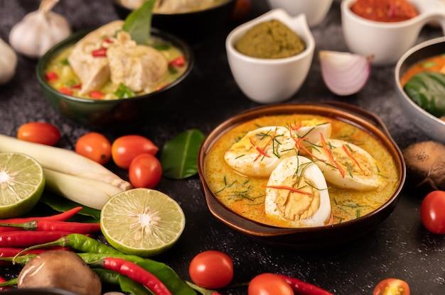 Grünes curry mit eiern in schwarzen tassen, mit zitrone, zitronengras, chili und tomaten.