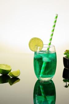 Grünes eisdrink mit zitrone auf reflektierend dunkem hintergrund