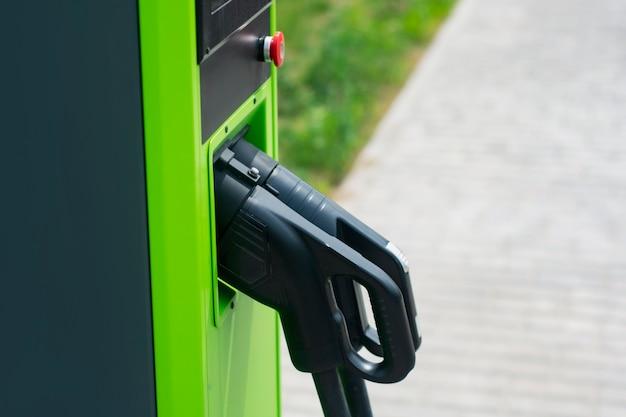 Grünes elektroauto, das am kraftwerk auflädt. umweltfreundliche tankstelle für öko-auto.