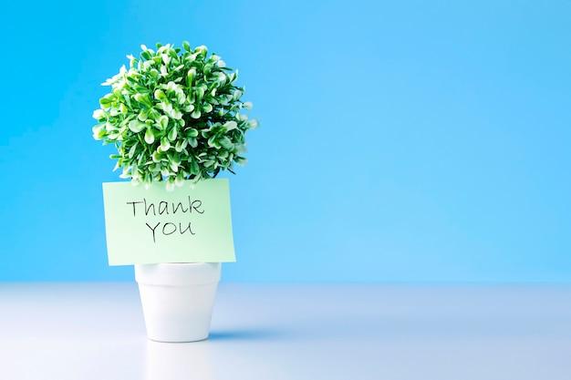 Grünes etikett mit dankeschön auf baum vor blauem hintergrund.