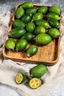 Grünes feijoa trägt in einer hölzernen platte auf einem grauen hintergrund früchte. tropische früchte feijoa. ansicht von oben