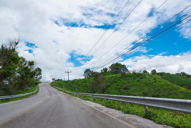 Grünes feld und wolken der straße auf blauem himmel am sommertag