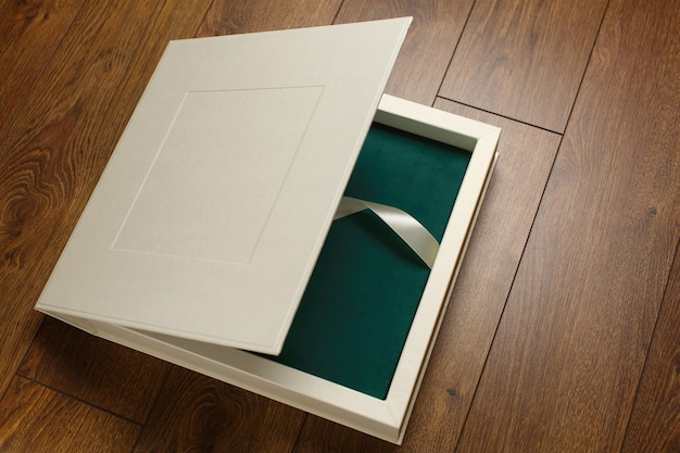 Grünes fotobuch mit textilbezug in beiger schachtel mit schönem karton für fotoalbum