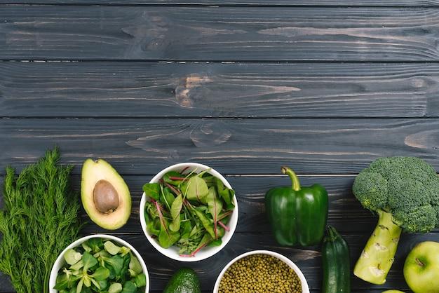 Grünes frischgemüse auf schwarzem hölzernem schreibtisch