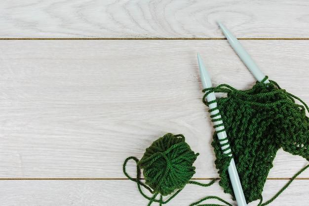 Grünes garn, das mit nadeln auf hölzernem hintergrund häkelt und strickt
