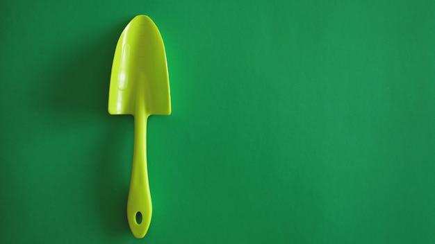 Grünes gartenwerkzeug auf grünem hintergrund - draufsicht und exemplar