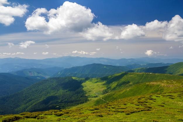 Grünes gebirgspanorama unter blauem himmel am hellen sonnigen tag. tourismus- und reisekonzept, kopierraum