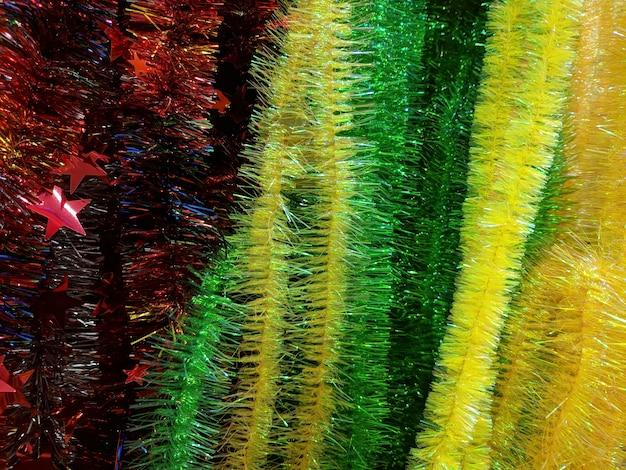 Grünes gelbes und rotes weihnachtslametta. mehrfarbige dekorationen für die feier des neuen jahres. textur.