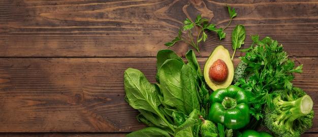 Grünes gemüse der gesunden nahrung auf hölzerner hintergrundoberansicht