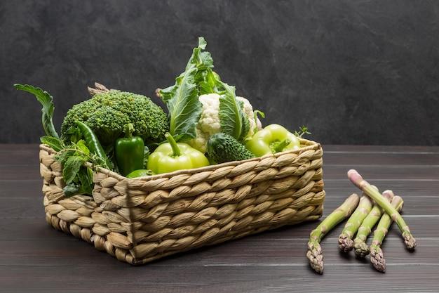 Grünes gemüse im rattankorb. spargel auf dem tisch. hölzerner hintergrund. platz kopieren