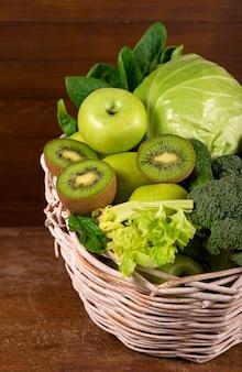 Grünes gemüse - kiwi, kohl, kräuter, sellerie, brokkoli, gurken in einem korb einen hölzernen hintergrund