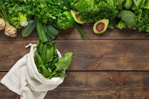 Grünes gemüse mit netzbeutel auf hölzernem grund. bestellen sie frisches lebensmittelgeschäft konzept