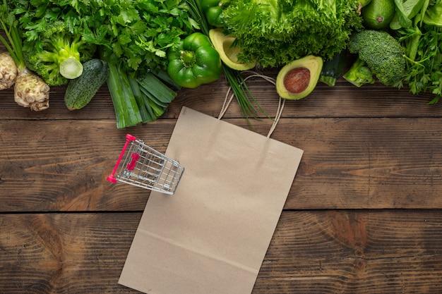 Grünes gemüse mit papiertüte und einkaufswagen auf hölzernem grund. bestellen sie frisches lebensmittelgeschäft konzept