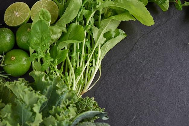 Grünes gemüse und dunkler blattnahrungsmittelhintergrund als gesundes ernährungskonzept des frischen gartens produzieren biologisch angebautes als symbol der gesundheit.