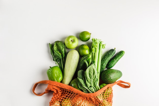 Grünes gemüse und früchte in der orange schnurtasche
