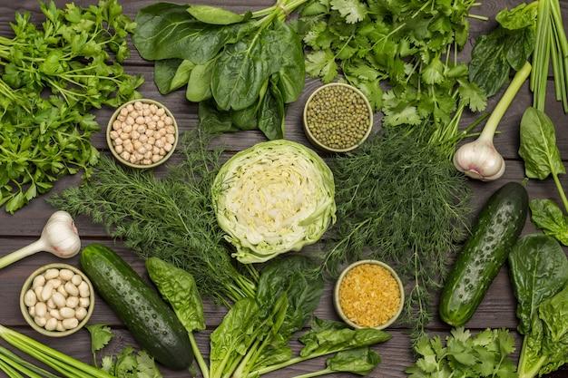Grünes gemüse und kichererbsen, bulgur, mungobohnen, nüsse. knoblauch, kohl und grüns auf dem tisch. dunkler hölzerner hintergrund. flach liegen.