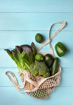 Grünes gemüse und obst in einem wiederverwendbaren stringbeutel auf hellblauem hintergrund