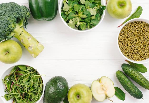 Grünes gemüse vereinbarte in kreisform auf weißem plankenbrett