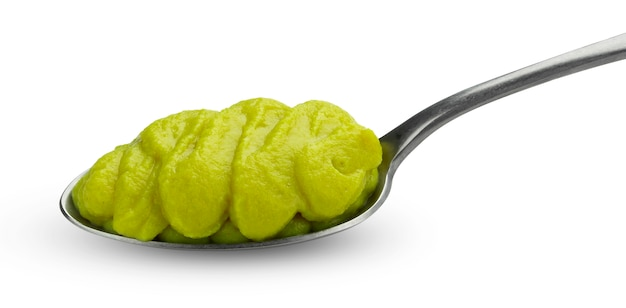 Grünes gemüsepüree für säuglingsnahrung im löffel lokalisiert auf weiß