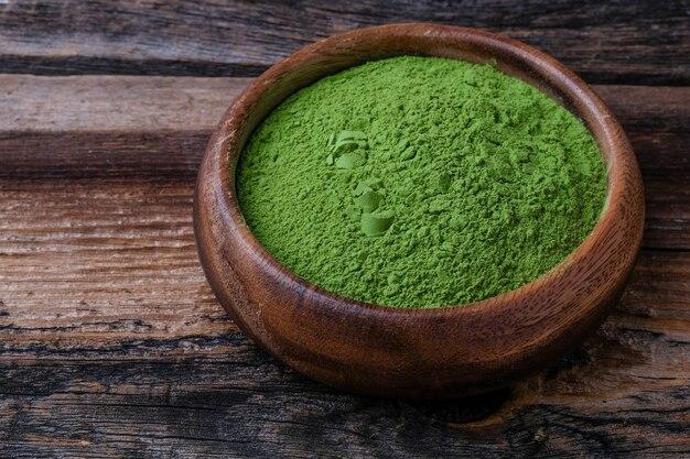 Grünes gemüsepulver auf holzschale bei holz