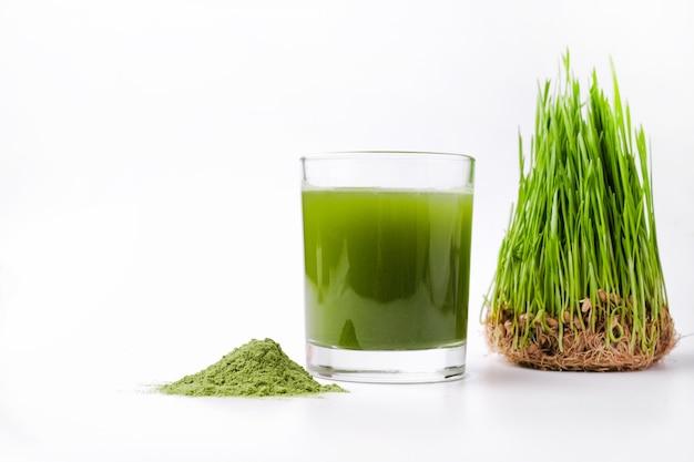 Grünes gerstensprossengras und schüssel mit grünem entgiftungspulver isoliert auf weißem hintergrund on