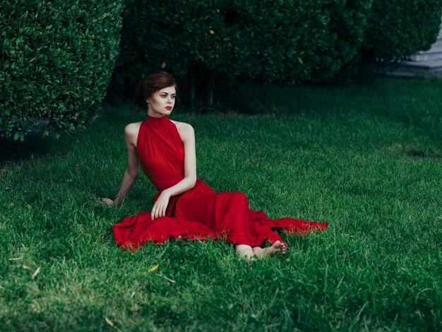 Grünes gras der schönen frau des roten kleides glamour naturgras.