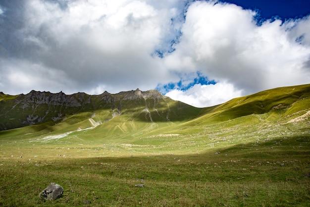 Grünes gras der sommerberge und landschaft des blauen himmels