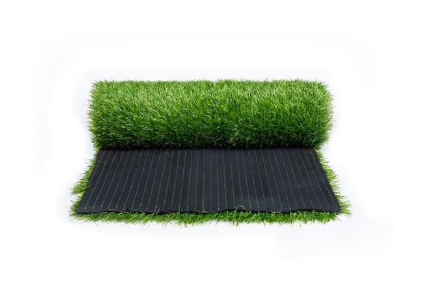 Grünes gras, rolle des kunstrasens, beschichtung lokalisiert auf weißer wand.