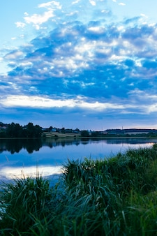 Grünes gras über dem idyllischen see mit blauem drastischem himmel