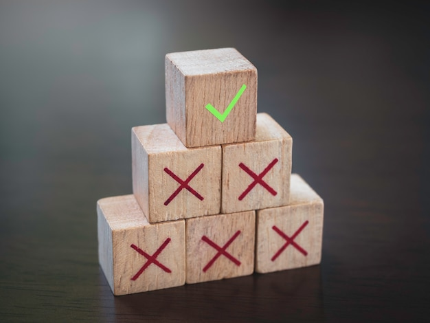 Grünes häkchen-symbol auf roten kreuzsymbolen auf hölzernen würfelblöcken, pyramidenstufen, auf holztischhintergrund. geschäftserfolg mit prozessmanagement, problemlösungskonzept.