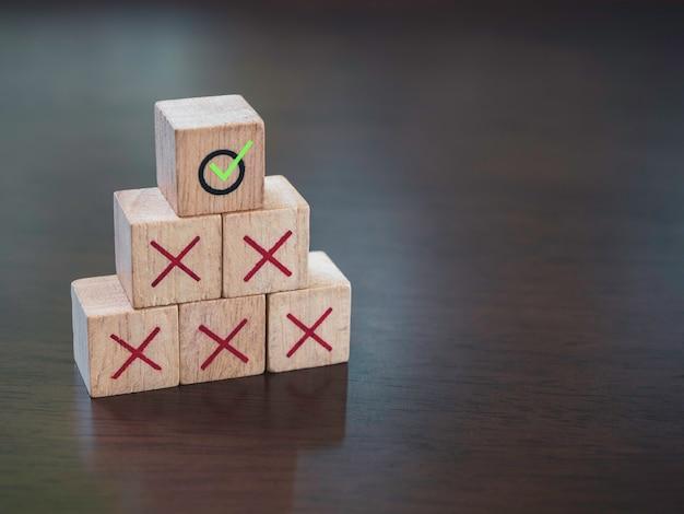Grünes häkchen-symbol auf roten kreuzsymbolen auf hölzernen würfelblöcken, pyramidenstufen, auf holztischhintergrund mit kopierraum. geschäftserfolg mit prozessmanagement, problemlösungskonzept.