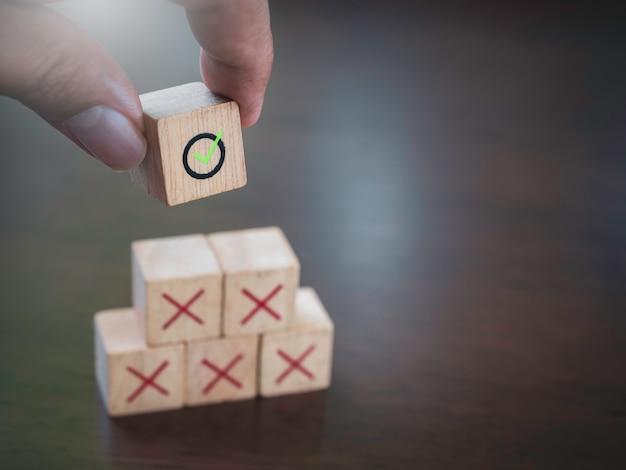 Grünes häkchen-symbol in der hand, das rote kreuzsymbole auf hölzernen würfelblöcken, pyramidenstufen, auf holztisch mit kopierraum aufsetzt. geschäftserfolg mit prozessmanagement, problemlösungskonzept.
